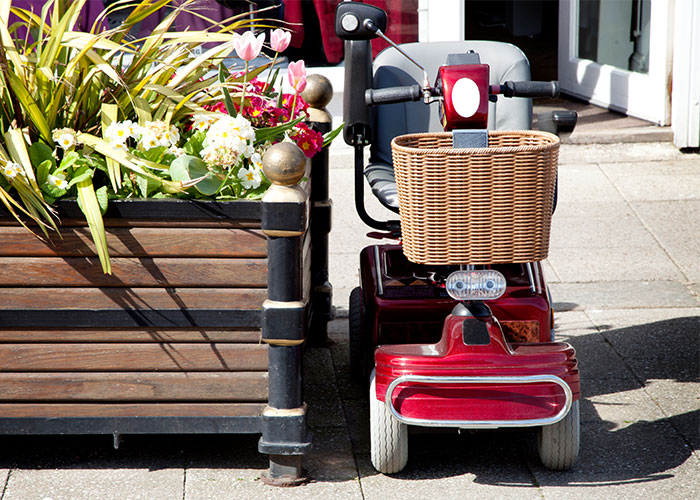Image of a power mobility wheelchair parked next to a flower basket